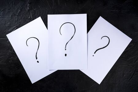 Question marks, written in ink on a piece of standard office paper, shot from the top on black Archivio Fotografico