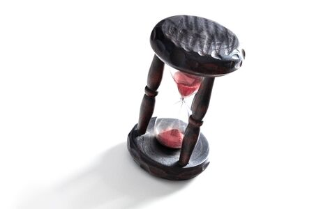 Time concept. A vintage hourglass with sand falling through, on a white background with copy space