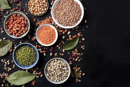 Legumes flatlay assortment, shot from above on a black background with copy space. Lentils, soybeans, chickpeas, red kidney beans, a vatiety of pulses