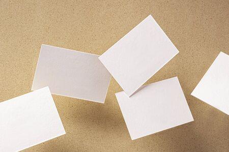 White business cards, floating on a brown paper background, a mock-up for design presentation Foto de archivo