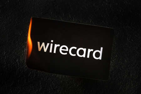 Madrid, Spain - June 27, 2020: Wirecard prepaid card burning on fire following the company bankruptcy and the freezing of cardholders money