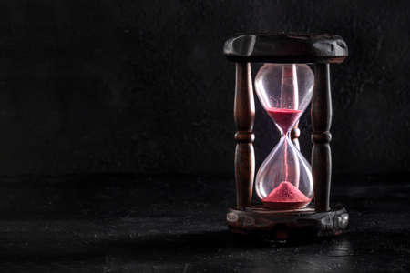 Time concept. An hourglass on a black background