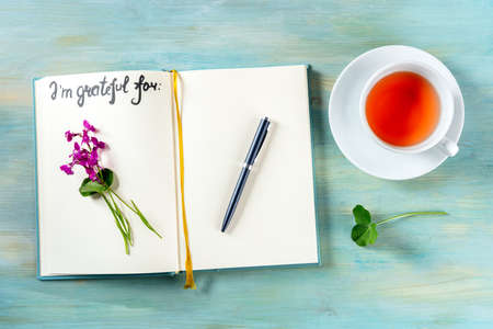 Gratitude journal with a pen and a cup of tea, with the handwritten phrase I am grateful for and a flower