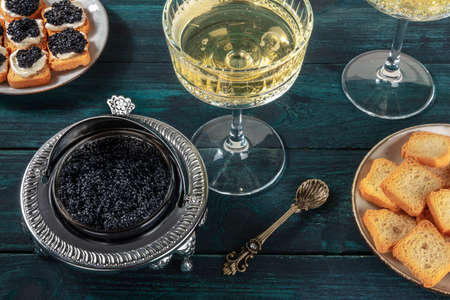 Caviar in a vintage bowl with a champagne coupe glass, with bread and toasts