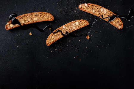 Cantucci. Traditional Italian almond cookies, shot from above on a black background with chocolate