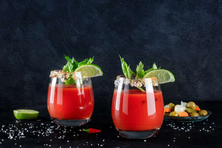 Bloody Mary cocktails on a dark background with copy space, a side view