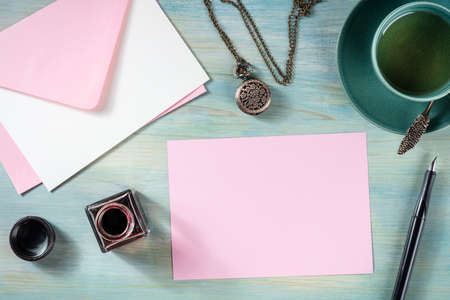 Pink greeting card or invitation design template, shot from the top with other stationery, ink and tea