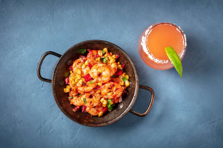 Spicy shrimps and a Paloma cocktail, overhead shot