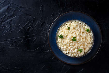 Rice with parsley, top-down shot on a black background