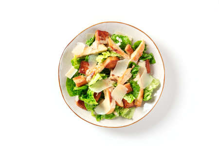 Caesar salad with grilled chicken meat, romaine and Parmesan, shot from the top