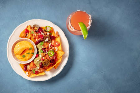 Nachos with chili con carne and a Paloma cocktail, shot from above