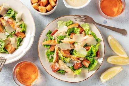 Chicken Caesar salad, overhead flat lay shot with wine