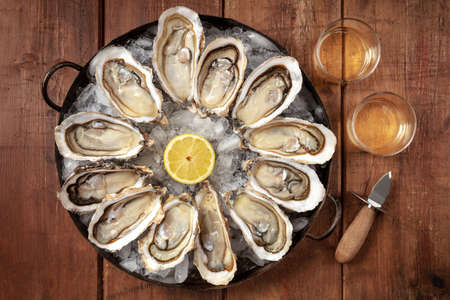 Oysters with wine, lemon, and a shucking knife 版權商用圖片