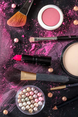 Makeup products and tools, overhead flat lay shot on a dark background