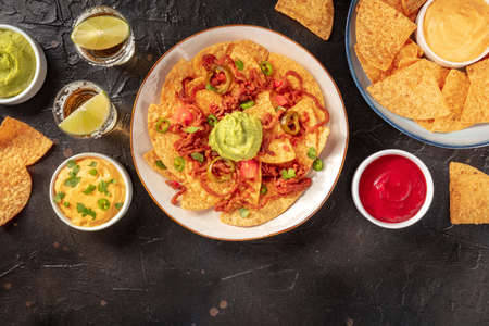 Nachos with dips and tequila, overhead flat lay shot Stock Photo
