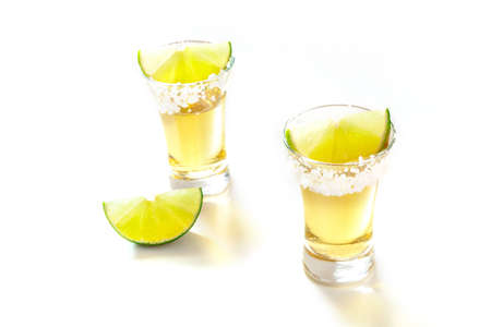 Tequila shots with lime slices on white 写真素材