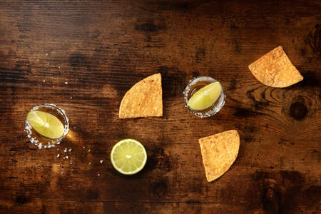 Tequila with lime and nacho chips, overhead flat lay shot 写真素材
