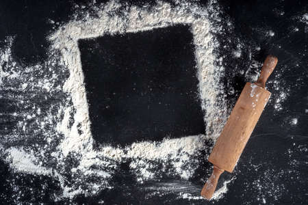 Baking frame with copy space, white flour and a wooden rolling pin 写真素材