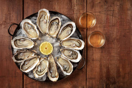 Oysters. A dozen of raw oysters, shot from the top on a wooden background 写真素材