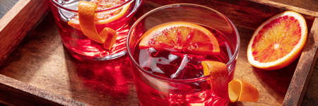Negroni cocktails with blood oranges panorama on a rustic background