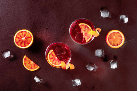 Negroni cocktails, toned image. Blood oranges, glasses with orange peel