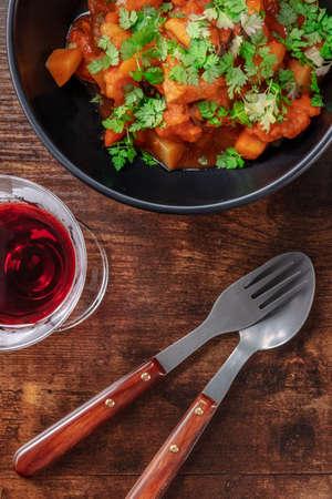 The cuisine of Portugal. Alentejo style pork with a glass of sweet porto wine Archivio Fotografico