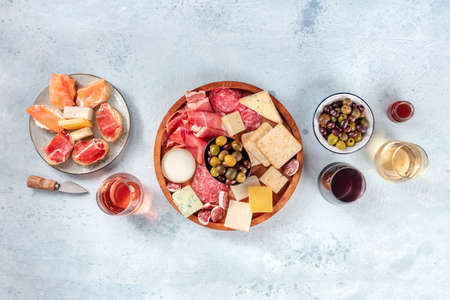 Charcuterie and cheese board, overhead flat lay shot with copy space. Italian antipasti, shot from above with wine, olives, and sanwiches. Mediterranean delicatessen