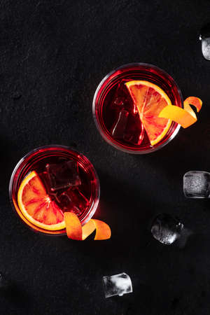 Negroni cocktails with orange rind, shot from the top with ice cubes on a black background, with copy space