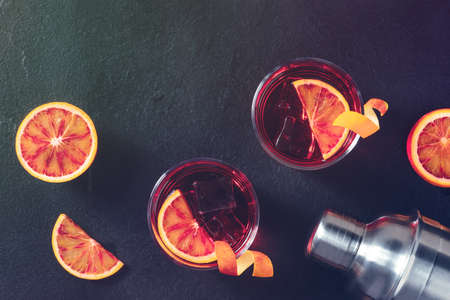 Orange cocktails, toned atmospheric image, with blood oranges and a shaker, overhead shot with copyspace