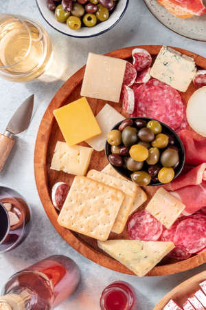 Charcuterie and cheese board close-up with wine and olives, shot from above. Italian antipasti or Spanish tapas. Ham, blue cheese and other gourmet snacks