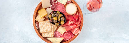 Charcuterie and cheese plate panorama, shot from the top with rose wine. Cold meats, blue cheese, olives. Delicatessen with a drink