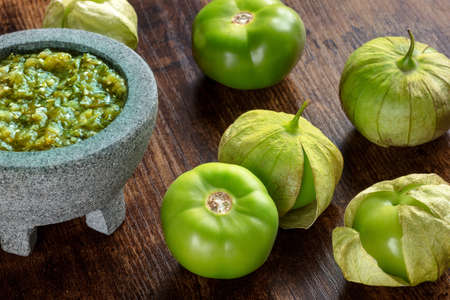 Tomatillos, green tomatoes, with salsa verde, green sauce, in a molcajete, traditional Mexican mortar, on a dark rustic wooden background