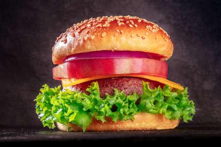 Burger close-up on black. Fat beef patty steak with green salad, Cheddar cheese, beefsteak tomato, purple onion and a sesame bun 版權商用圖片