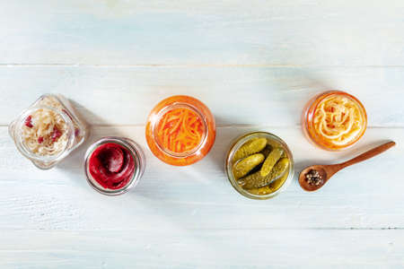 Fermented food. Canned vegetables. Pickled carrot, beetroot, sauerkraut and other organic preserves in mason jars, shot from the top on a rustic wooden background with copy space