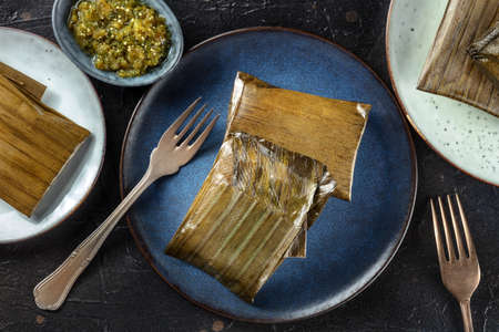 Tamal, traditional dish of the cuisine of Mexico, various stuffings wrapped in green leaves. Hispanic food, overhead flat lay shot on a black background, with salsa verde