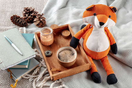 Hygge still life with a toy fox, a cup of coffee, and scented candles. Cozy weekend morning, staying at home in cold weather