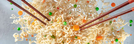 Flying instant noodles with two pairs of chopticks panorama. Ramen cup with carrot and green peas panoramic banner 版權商用圖片