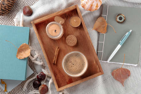 Hygge. Autumn still life with coffee, candles, fall leaves, a journal, and some books, overhead flat lay shot