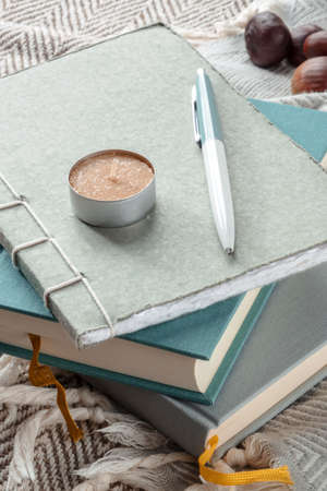 Hygge. A journal and a scented candle. Notebooks on a blanket, lazy winter morning. Comfy still life