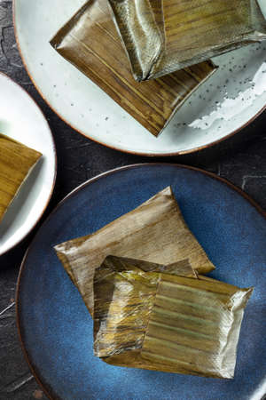 Tamales oaxaquenos, traditional Hispanic dish, wrapped in green leaves, shot from the top on a black background. Mexican Candelaria meal