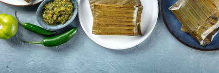 Tamal overhead flat lay panorama with copy space. Traditional dish of the cuisine of Mexico, various stuffings wrapped in green leaves. Hispanic food. With chili peppers and tomatillos