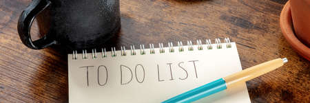 To do list panorama with a ballpoint pen on a wooden background. A paper notebook with the handwritten words 版權商用圖片