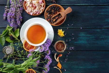 Tea banner with herbs, flowers and fruit, top shot on a dark rustic wooden background with copy space