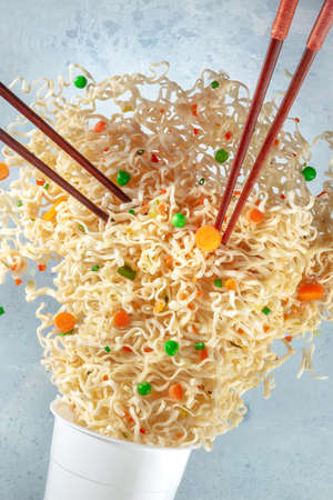 Ramen cup with noodles flying out of it and two pairs of chopsticks, a close-up. Instant noodle meal with carrots and green peas