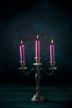 Candle magic. Purple candles in a vintage candleholder on a dark background 版權商用圖片