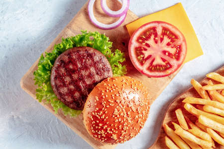 Burger ingredients with French fries. Hamburger beef patty steak with a sesame bun and vegetables, top shot 版權商用圖片