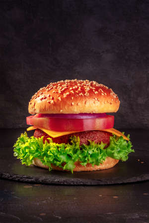 Burger on black with copy space. Beef patty steak with lettuce, cheese, tomato, onion and a sesame bun