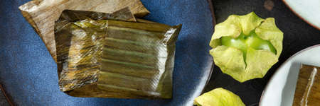 Tamal panorama with tomatillo. Traditional dish of Mexican cuisine, overhead flat lay shot with tomatillos. Various stuffings wrapped in green leaves. Hispanic food 版權商用圖片