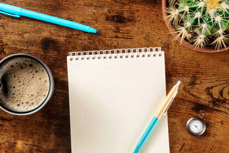 Stationery mockup. Blank notebook with blue pens and coffee, shot from the top on a wooden background, a flat lay business composition