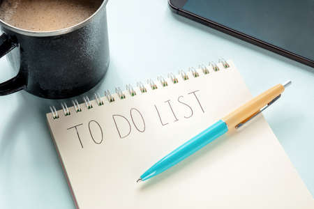 To do list. A paper notebook with coffee, a blue pen, and a mobile phone. The concept of planning, time management etc